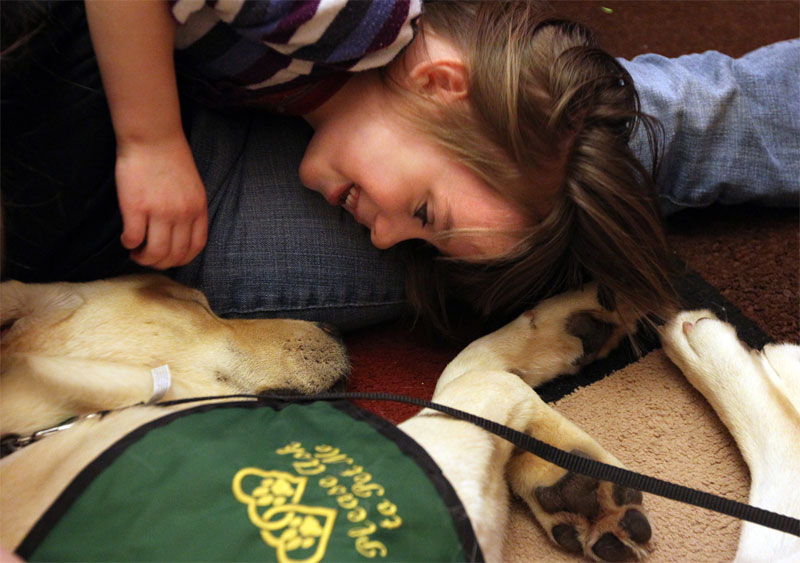 A girl rests near an autism therapy dog